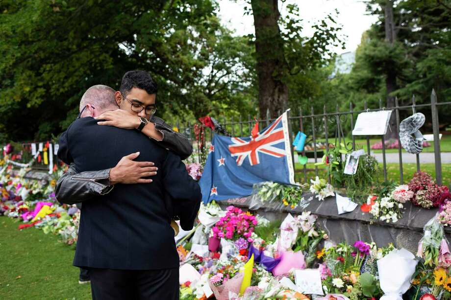 Mourners comfort each other at a makeshift memorial near Al Noor mosque in Christchurch, New Zealand. After that massacre, New Zealand took immediate action to prevent future mass shootings. How many mass shootings must occur here before lawmakers act? Photo: CORNELL TUKIRI /NYT / NYTNS