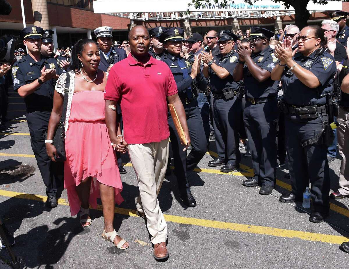 Members of the New Haven Police Department applaud as Captain Anthony Duff leaves Yale New Haven Hospital with his wife on August 22, 2019 a week after he was shot intervening in a shooting while off-duty.