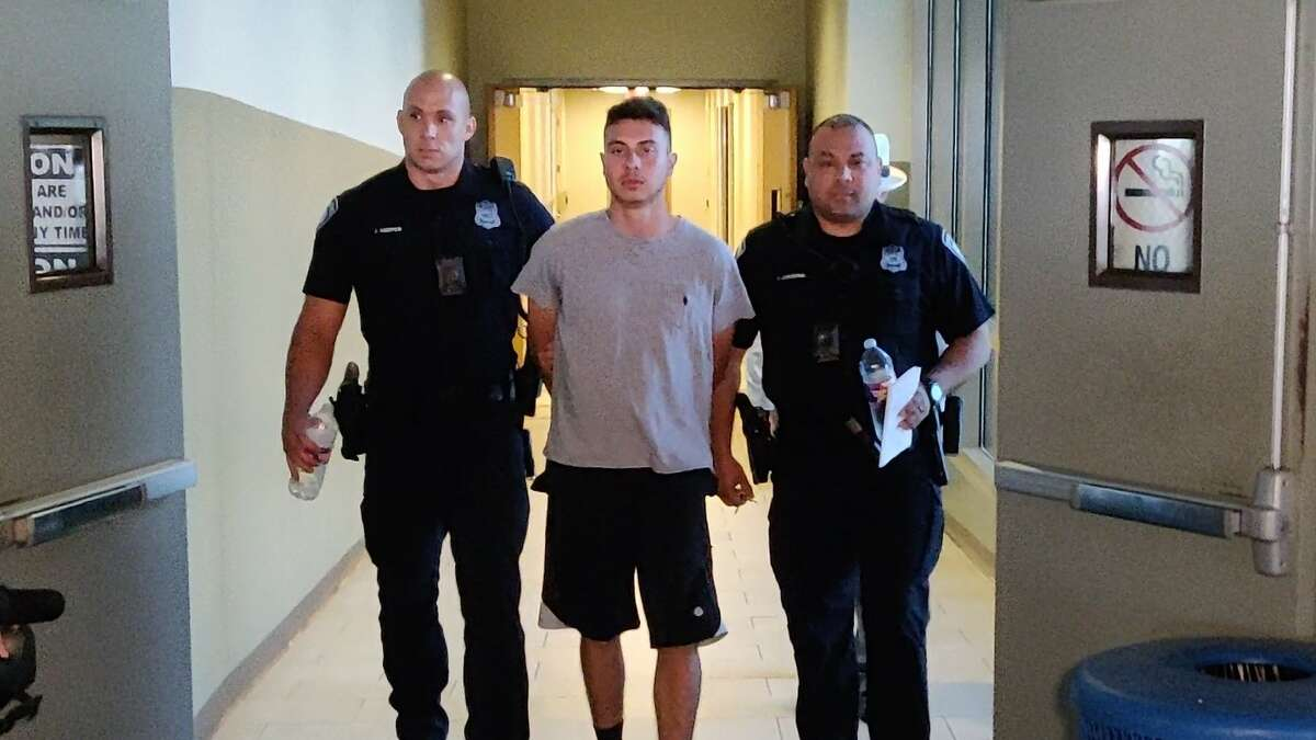 Sebastian Angel Espinar, 20, is charged with capital murder in the death of Andres Gerardo Salinas, 22, according to San Antonio Police. He is seen being escorted by officers to a police vehicle Thursday afternoon, Aug. 22, 2019, in the parking garage of the Public Safety Headquarters, 315 S. Santa Rosa Ave.