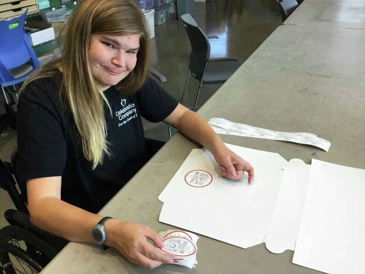 A Celebration Company employee affixes stickers on boxes Three Brothers Bakery buys to helps adults with disabilities improve their work and life skills.