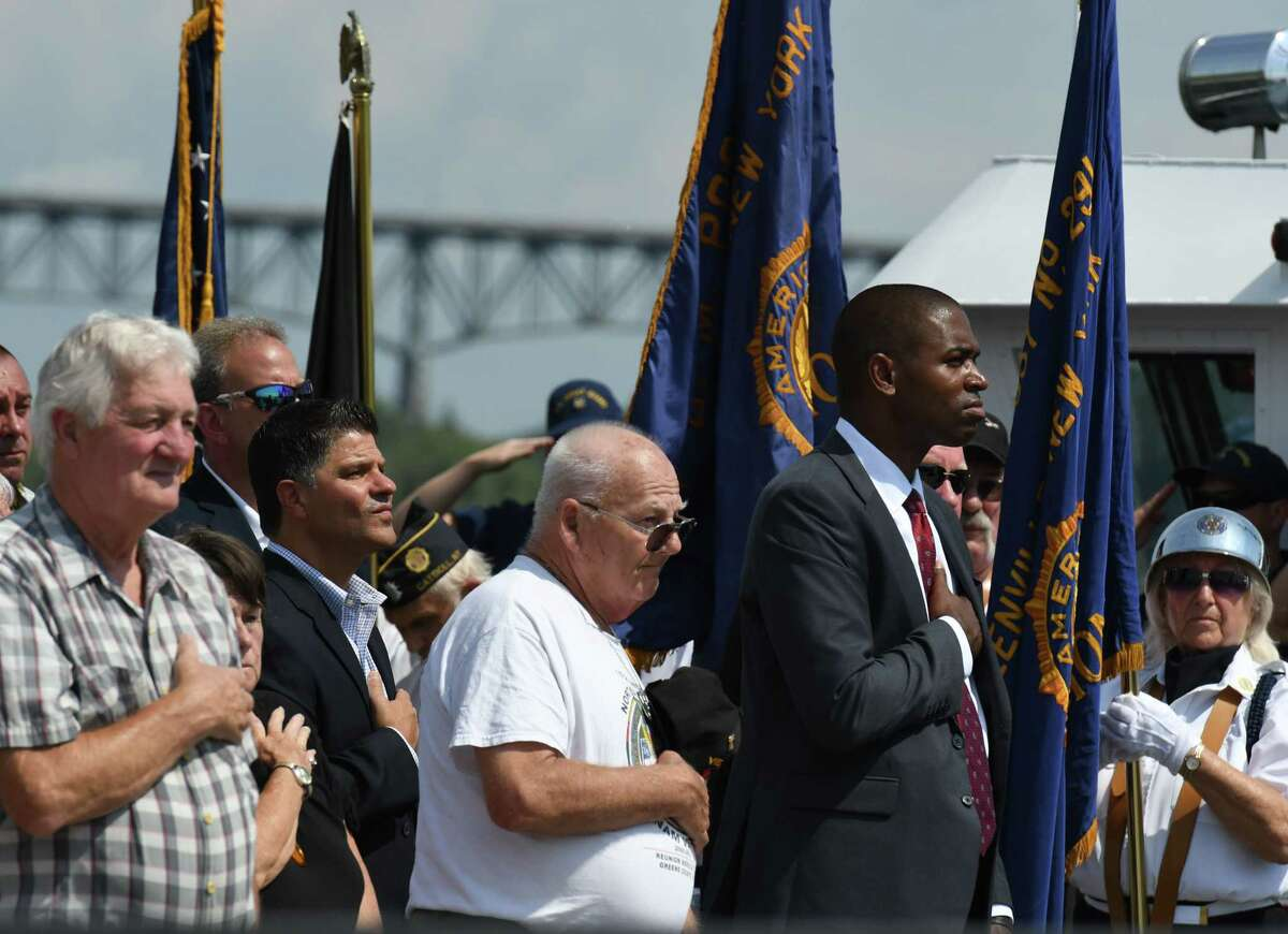 State Sen. George A. Amedore Jr., second from left, and U.S. Rep. Antonio Delgado, right, stand during a singing of