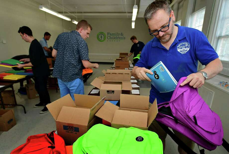 Volunteers from Albourne America, a local alternative investment firm, including Christos Koulladis, fill 80 backpacks with school supplies for children in Family & Children's Agency programs Thursday at the FCA facility at Ben Franklin School in Norwalk. The backpacks were filled with scientific calculators, pencils, notebooks, folders, and school supplies, were donated by High Water Women, a nonprofit founded by women in hedge fund and investment industries with the goal of providing enriched educational opportunities for children from low-income families. Photo: Erik Trautmann / Hearst Connecticut Media / Norwalk Hour