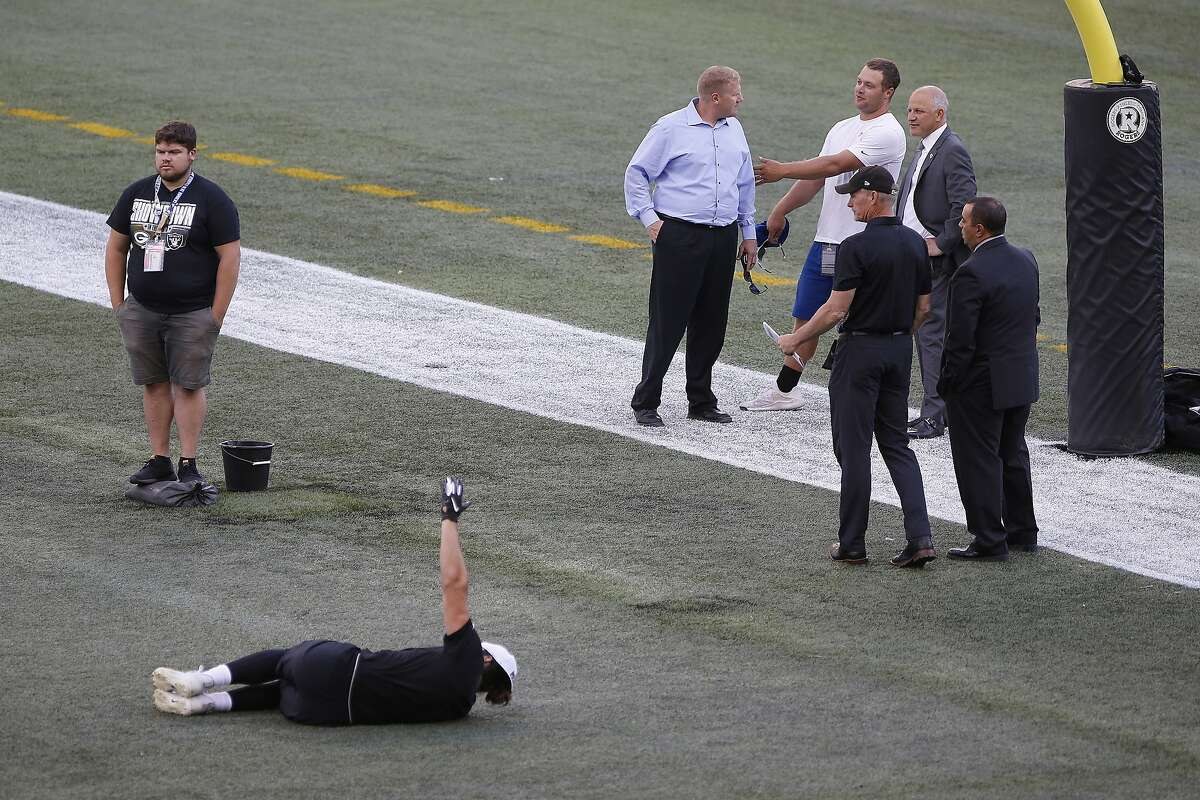 Officials assess the location where the CFL goal post holes were, before an NFL preseason football game between the Oakland Raiders and the Green Bay Packers in Winnipeg, Manitoba, Thursday, Aug. 22, 2019. In the NFL the field goal posts are located at the back of the end zone and the Canadian Football League has the posts at the front of the end zone. (John Woods/The Canadian Press via AP)