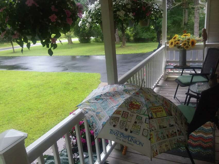 Longtime Times Union subscribers Ryan and Sandy Maloney of Valatie use a Times Union umbrella theya€™ve had for 20 years to a€?
