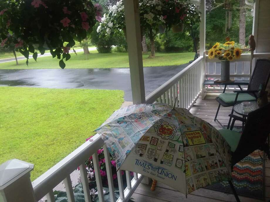 """Longtime Times Union subscribers Ryan and Sandy Maloney of Valatie use a Times Union umbrella theya€™ve had for 20 years to a€"""" fittingly a€"""" pick up their newspaper on rainy mornings. """"Thanks for keeping our paper dry,"""" they say."""