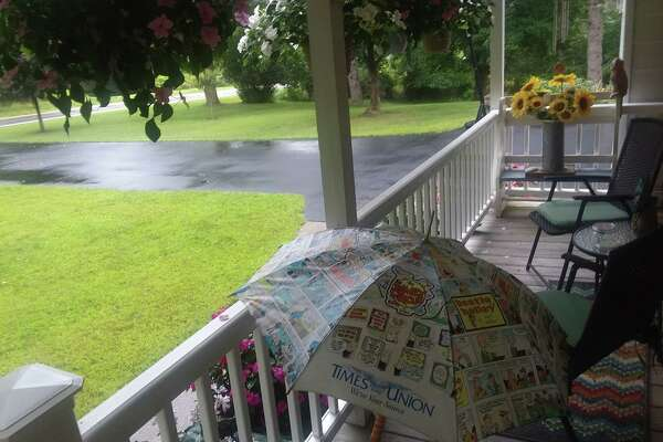 """Longtime Times Union subscribers Ryan and Sandy Maloney of Valatie use a Times Union umbrella theya€™ve had for 20 years to a€?"""" fittingly a€?"""" pick up their newspaper on rainy mornings. """"Thanks for keeping our paper dry,"""" they say."""