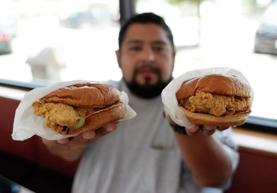 Randy Estrada holds up chicken sandwiches at a Popeyes, Thursday, Aug. 22, 2019, in Kyle, Texas. (AP Photo/Eric Gay) Photo: Eric Gay / Eric Gay / Associated Press / Copyright 2019 The Associated Press. All rights reserved.