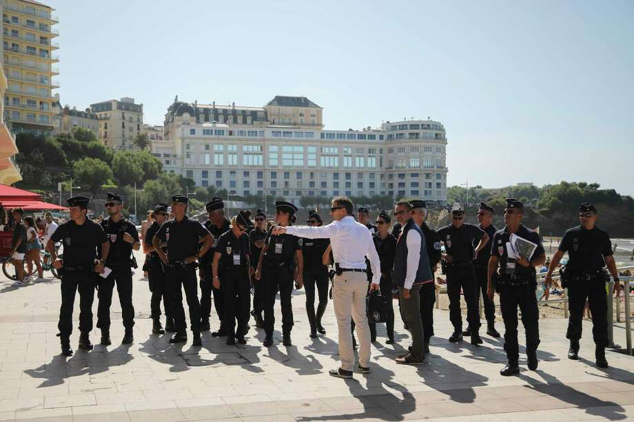 French police officers get instructions in front of the Le Bellevue at the beach promenade ahead of the upcoming G7 Summit, in Biarritz, France, Thursday, Aug. 22, 2019. The G7 Summit will host the heads of countries with advanced economies from United States, Britain, Canada, Germany, Italy, Japan and France and will be held in Biarritz between the 24th and 26th of August. (AP Photo/Markus Schreiber) Photo: Markus Schreiber / Copyright 2019 The Associated Press. All rights reserved
