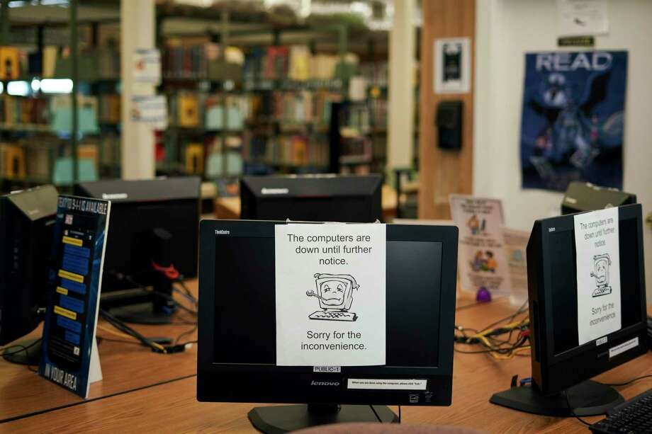 Computers are shut down at the E.M. Gilliam Memorial Library following a ransomeware attack in Wilmer, Texas, Aug. 22, 2019. As hackers lock up networks that power police forces and utilities, municipalities must operate with hobbled computer systems, and decide whether to pay ransoms. (Cooper Neill/The New York Times) Photo: COOPER NEILL, STR / NYT / NYTNS