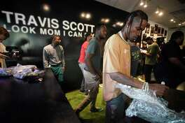 Rapper Travis Scott autographs on a VCR player during his Netflix pop-up event held at the Movie Exchange, 11200 NW Fwy., Thursday, Aug. 22, 2019, in Houston.