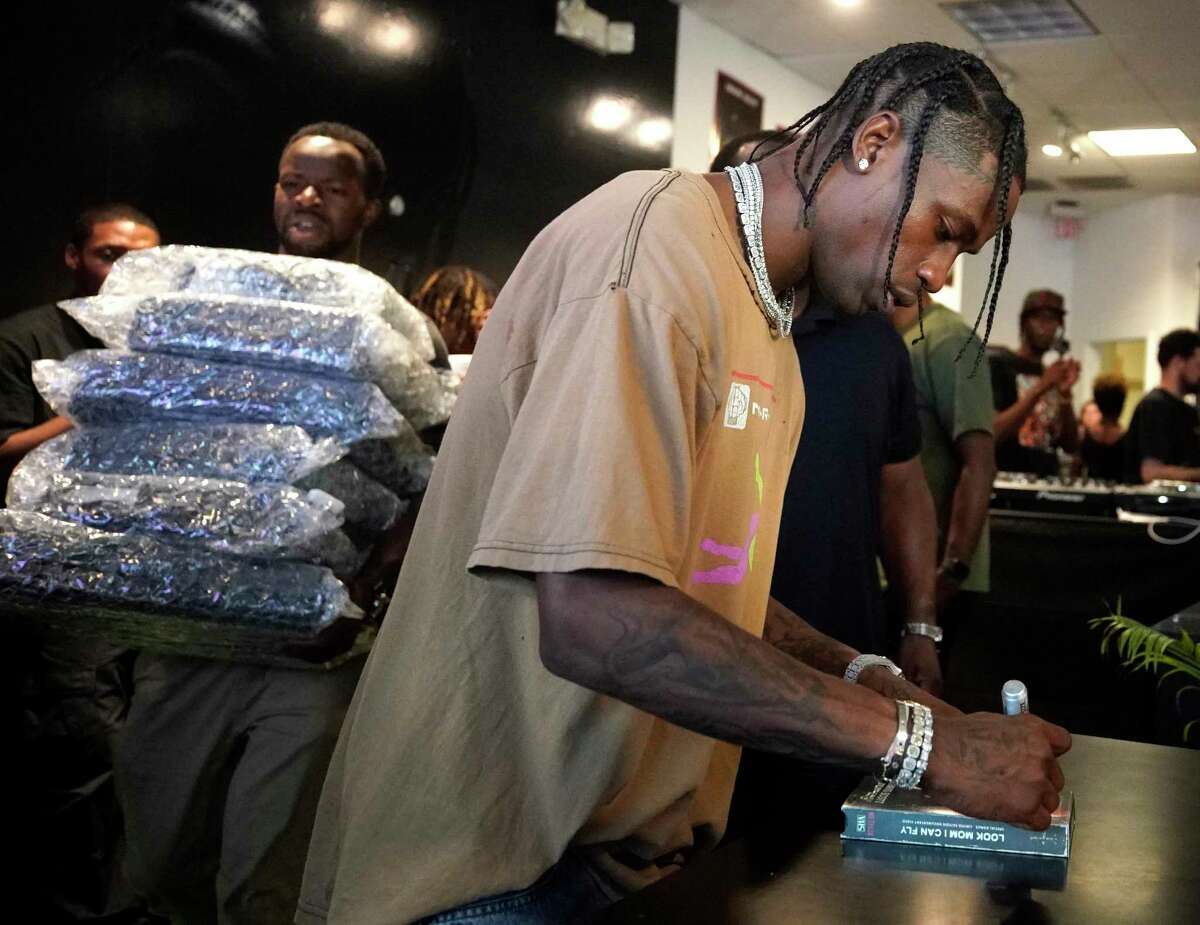 Rapper Travis Scott autographs a VHS tape as a stack of VCR players is carried to the counter during his Netflix pop-up event held at the Movie Exchange, 11200 NW Fwy., Thursday, Aug. 22, 2019, in Houston.