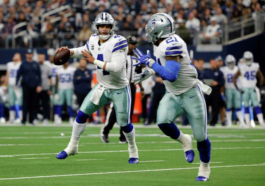 FILE - In this Dec. 23, 2018, file photo, Dallas Cowboys quarterback Dak Prescott (4) prepares to throw a pass to running back Ezekiel Elliott, right, during the second half of an NFL football game against the Tampa Bay Buccaneers in Arlington, Texas. Elliott, the two-time NFL rushing champion, has been holding out for a new deal before he enters his fourth season. He's due to make $3.9 million this year and $9.1 million in 2020. Elliott could eventually end up being the highest-paid running back in league history if the two sides agree. (AP Photo/Michael Ainsworth, File) Photo: Michael Ainsworth, FRE / Associated Press / Copyright 2018 The Associated Press. All rights reserved.