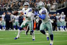 FILE - In this Dec. 23, 2018, file photo, Dallas Cowboys quarterback Dak Prescott (4) prepares to throw a pass to running back Ezekiel Elliott, right, during the second half of an NFL football game against the Tampa Bay Buccaneers in Arlington, Texas. Elliott, the two-time NFL rushing champion, has been holding out for a new deal before he enters his fourth season. He's due to make $3.9 million this year and $9.1 million in 2020. Elliott could eventually end up being the highest-paid running back in league history if the two sides agree. (AP Photo/Michael Ainsworth, File)