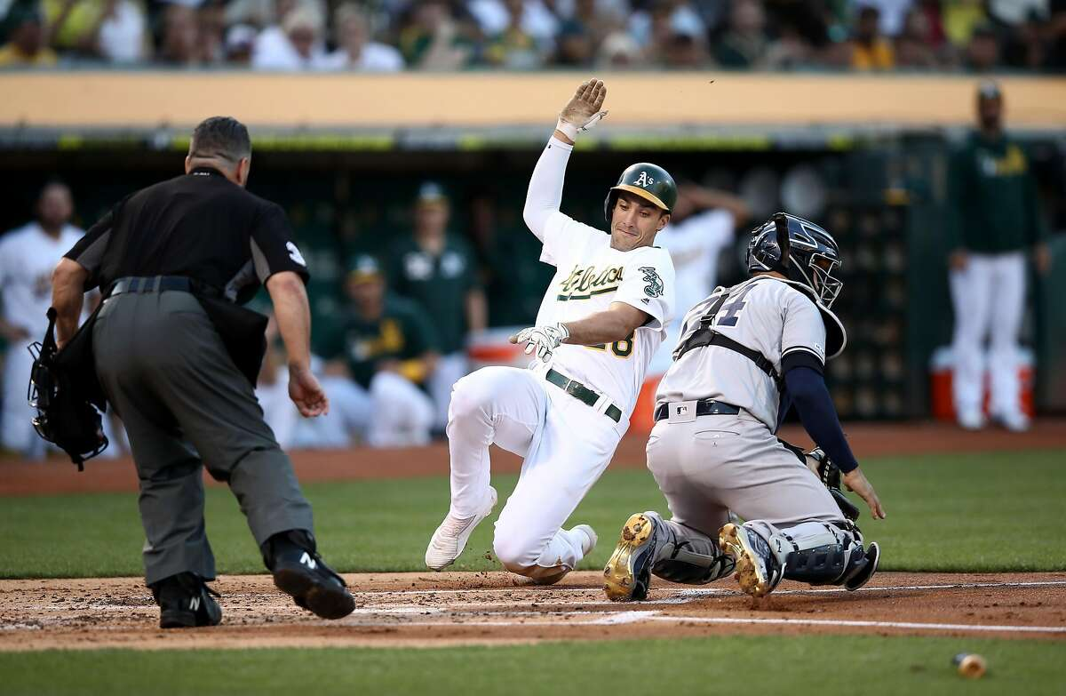 OAKLAND, CALIFORNIA - AUGUST 22: Matt Olson #28 of the Oakland Athletics slides past Gary Sanchez #24 of the New York Yankees to score on a hit by Mark Canha #20 in the first inning at Ring Central Coliseum on August 22, 2019 in Oakland, California. (Photo by Ezra Shaw/Getty Images)