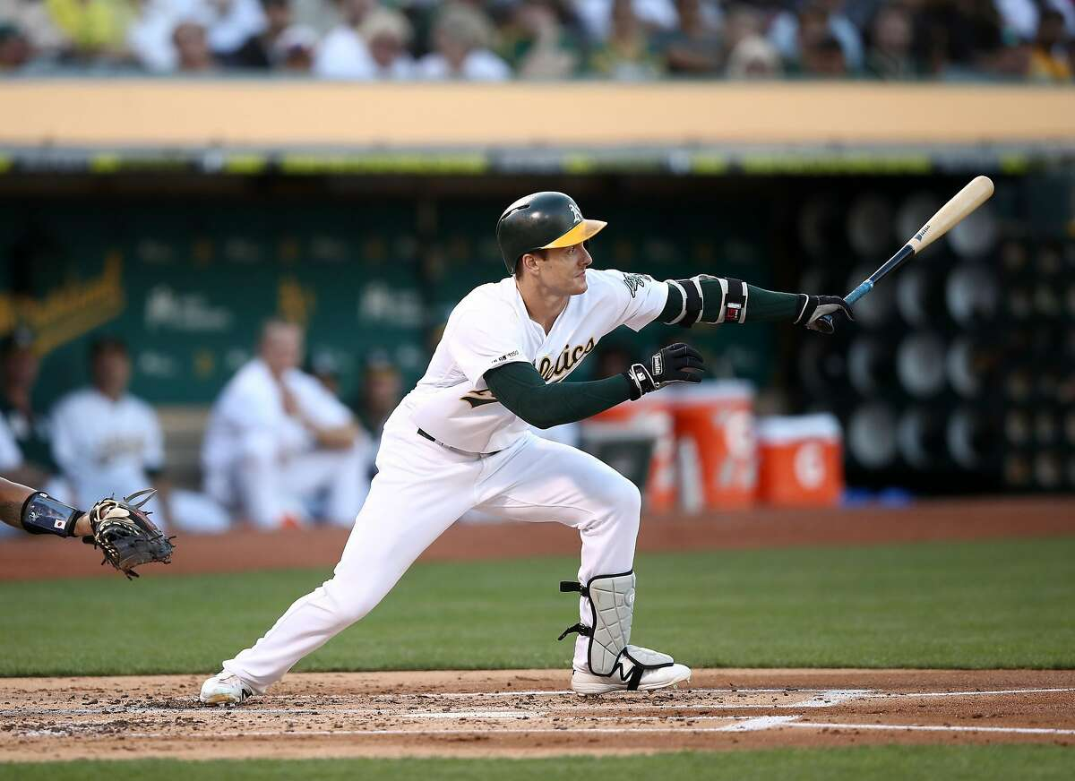 OAKLAND, CALIFORNIA - AUGUST 22: Mark Canha #20 of the Oakland Athletics hits a single that scored two runs in the first inning against the New York Yankees at Ring Central Coliseum on August 22, 2019 in Oakland, California. (Photo by Ezra Shaw/Getty Images)