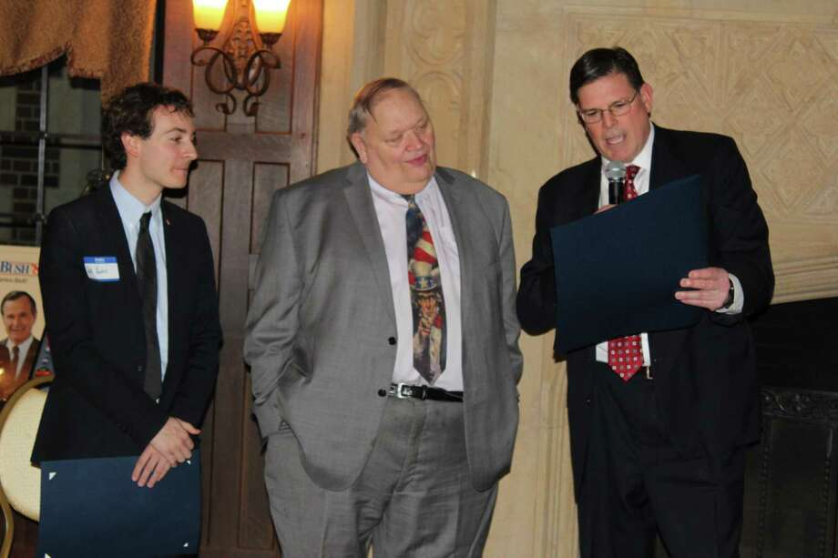 George Cody, center, who this week recalled his trip 50 years ago to Woodstock, listens as state Sen. Will Haskell, left, and state Rep. Thomas P. O'Dea read a citation during his retirement party last winter. Photo: John Kovach / Hearst Connecticut Media / New Canaan Advertiser