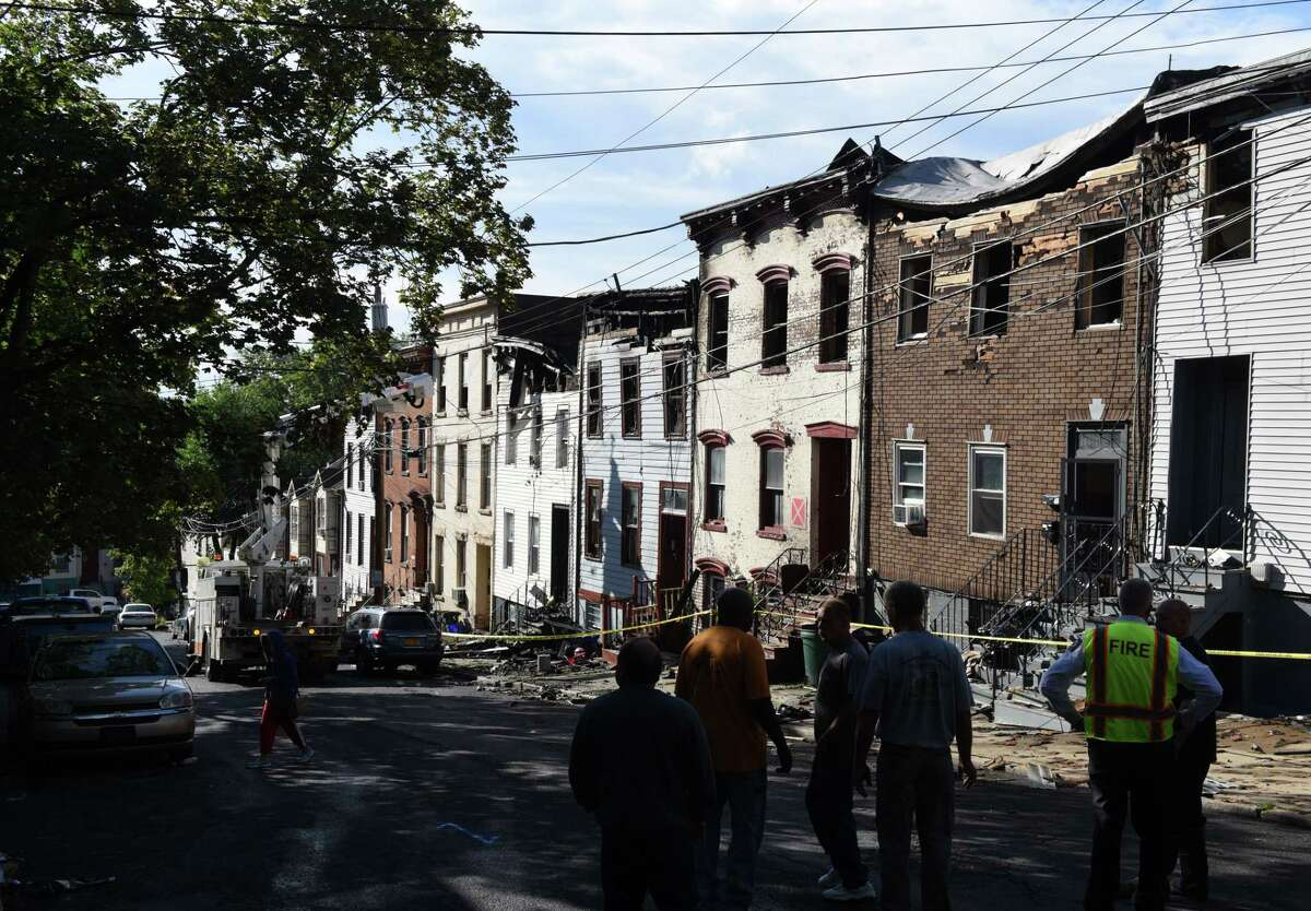 Crews work on investigation and cleanup after a massive fire engulfed several Myrtle Avenue homes overnight on Friday morning, Aug. 23, 2019, in Albany, N.Y. The blaze destroyed five buildings, the first of which was unoccupied. (Will Waldron/Times Union)