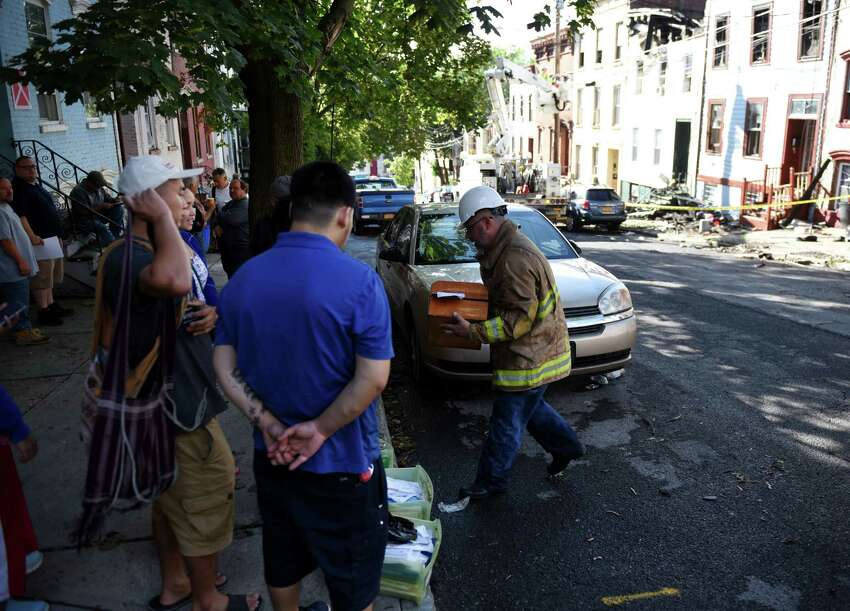 Belongings are recovered after a massive fire engulfed several Myrtle Avenue homes overnight on Friday morning, Aug. 23, 2019, in Albany, N.Y. The blaze destroyed five buildings, the first of which was unoccupied. (Will Waldron/Times Union)