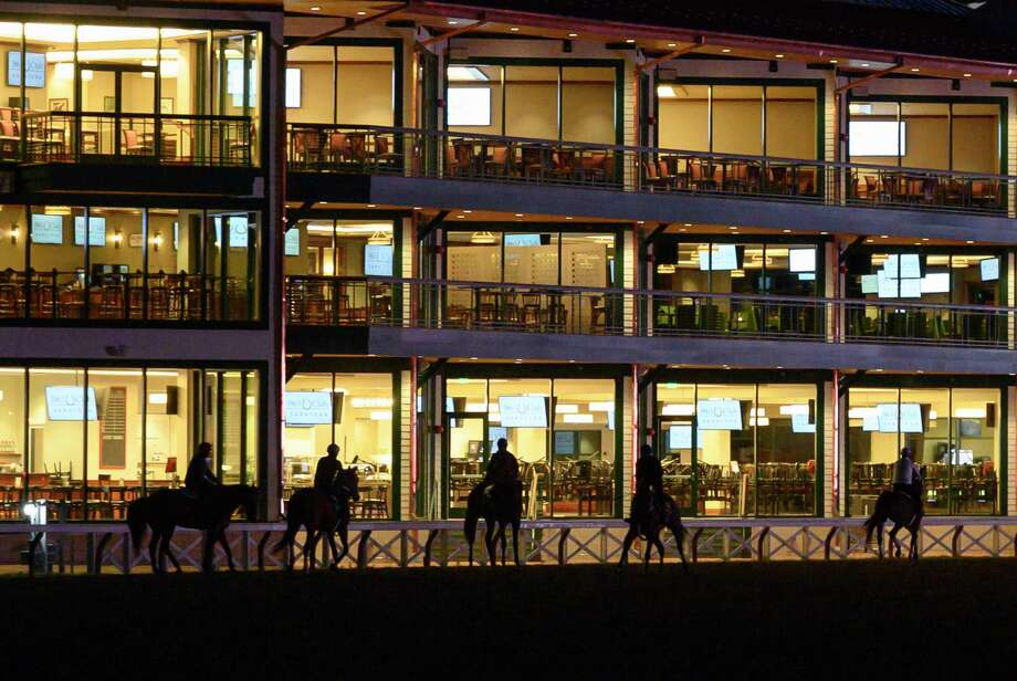 Horses are silhouetted in the lights of the 1863 Club on the main track during morning workouts before daybreak at the Saratoga Race Course Friday Aug. 23, 2019 in Saratoga Springs, N.Y. Photo special to the Times Union by Skip Dickstein