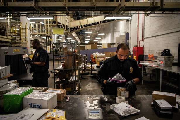 Sustoms and Border Protection officer Mohammed Rahman holds a bag later found to be filled with fentanyl at John F. Kennedy International Airport's mail facility in New York on Sept. 7, 2018.