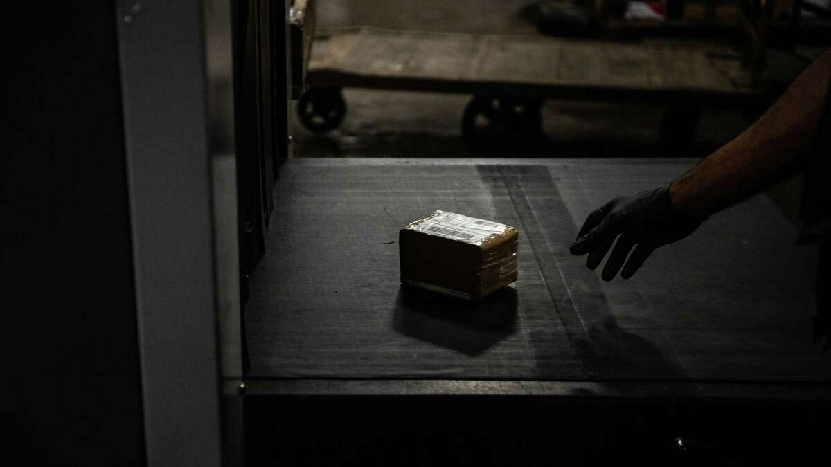 A package mailed from China is removed for additional search at John F. Kennedy International Airport's International mail facility in New York in 2018. The plastic bag of white powder in the box was found to contain fentanyl.