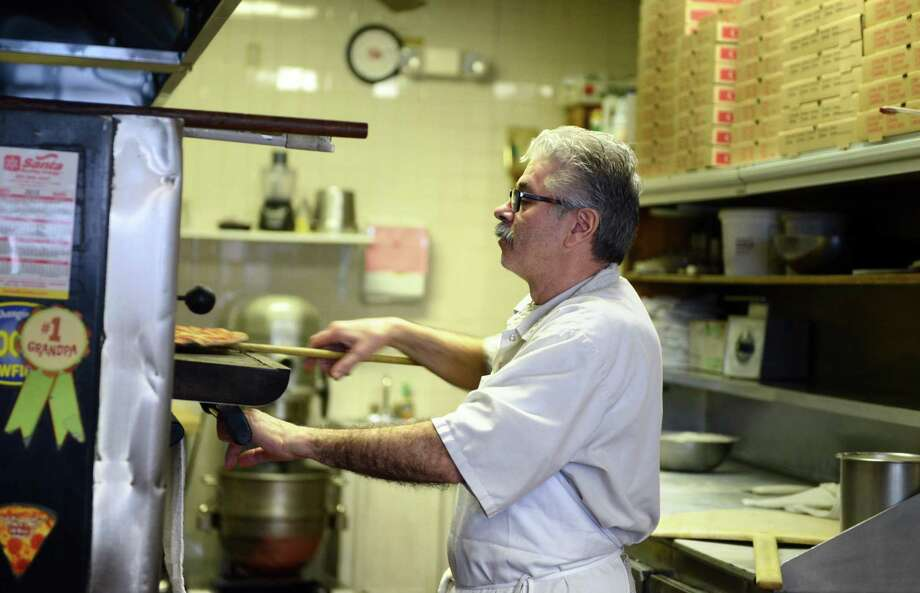 Franco Patrizi, owner of Franco's Pizza, pulls a pizza from the oven in his restaurant on River Street in Milford, Conn. Thursday, March 5, 2015. Photo: Autumn Driscoll / Autumn Driscoll / Connecticut Post