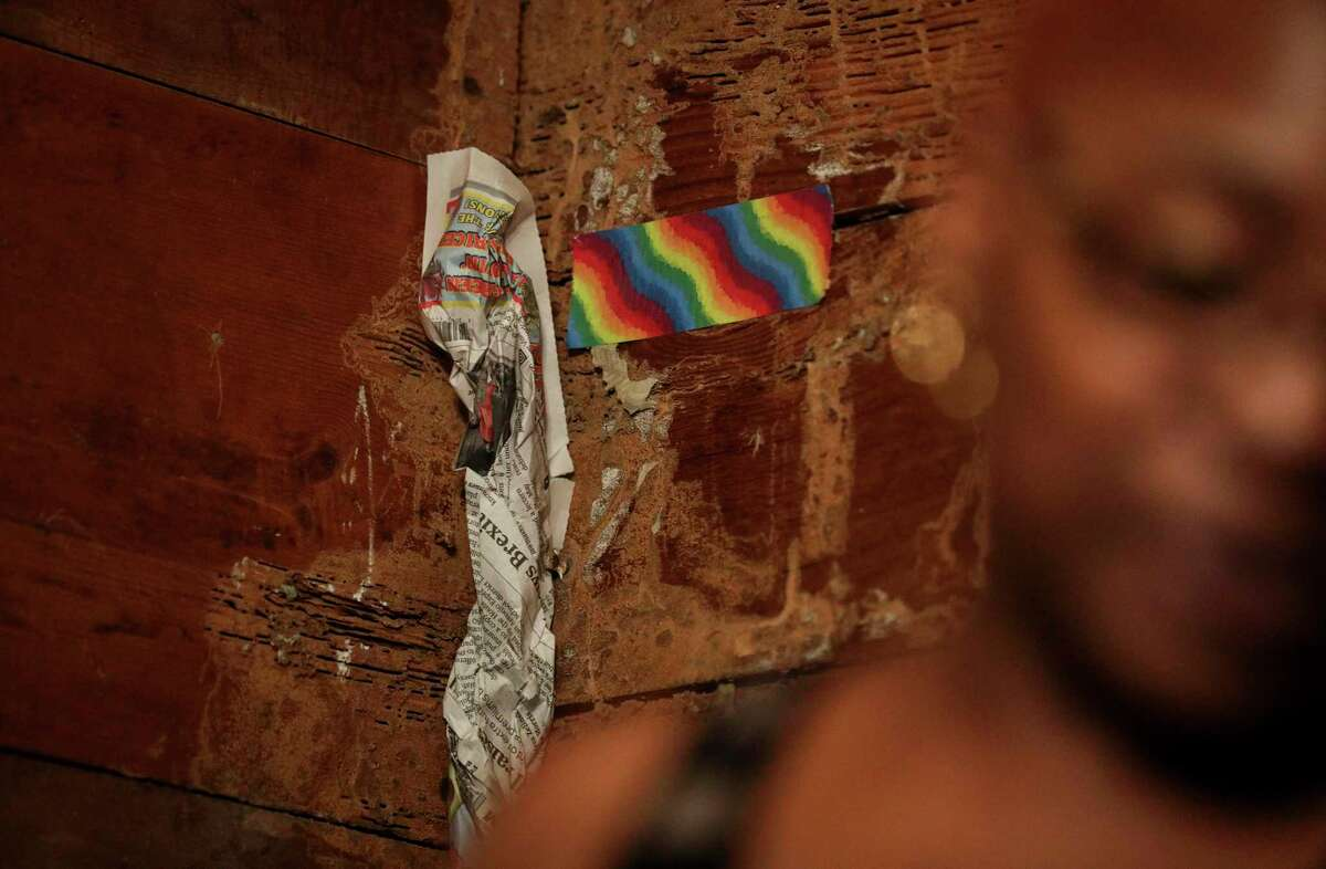"""Newspaper and tape cover holes in the walls of Sandra Edwards' home on Thursday, Aug. 15, 2019, in Houston. She said she covered them to keep animals and insects out. """"I don't do critters,"""" she said."""