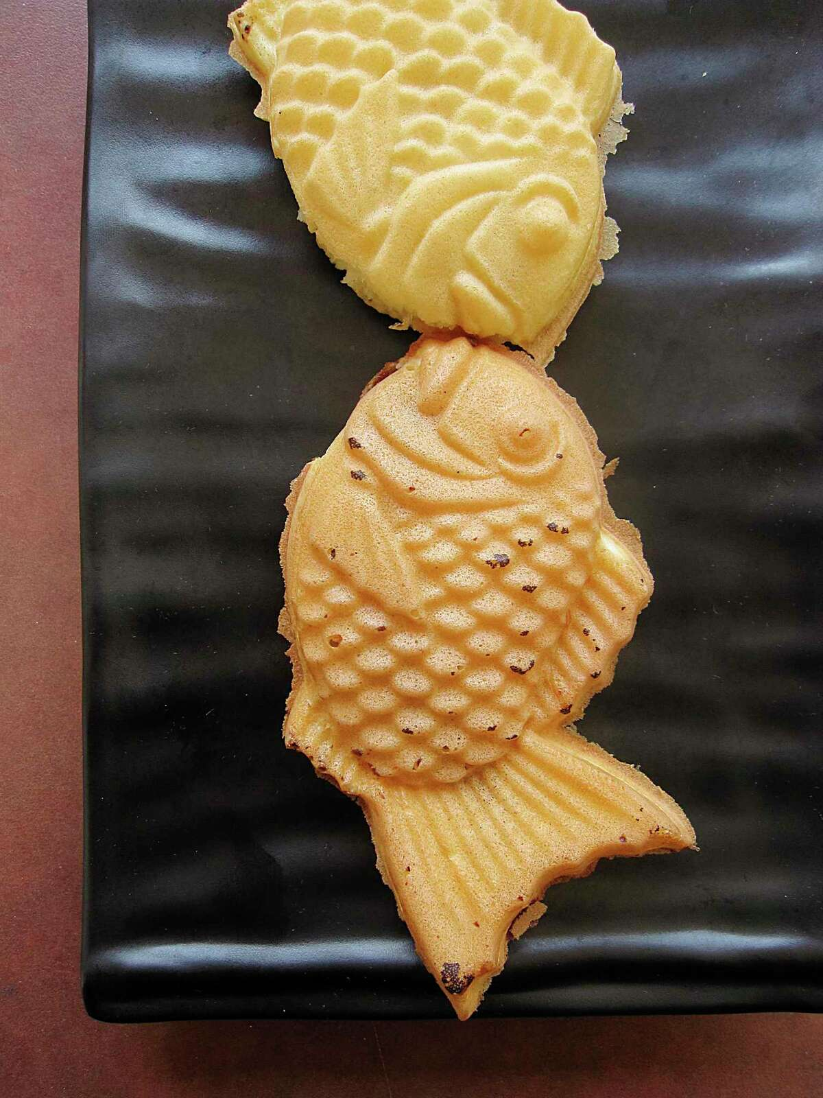 Fish-shaped cakes called taiyaki are filled with Nutella, bottom, and pineapple at Blue Whale.