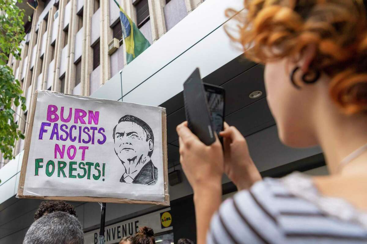 People protest in front of the Consulate General of Brazil in Geneva, Switzerland, Friday, Aug. 23, 2019 to denounce the words of President Bresil Jair Bolsonaro and the many fires in the forest Amazon.