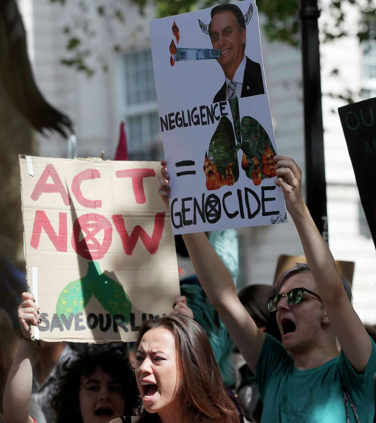Extinction Rebellion activists protest outside the Brazilian Embassy in London, Friday, Aug. 23, 2019, to call on Brazil's President Jair Bolsonaro to act to protect the Amazon rainforest. The European Union is throwing its weight behind French President Emmanuel Macron's call to put the Amazon fires on the agenda of this weekend's G-7 summit of world leaders in France.