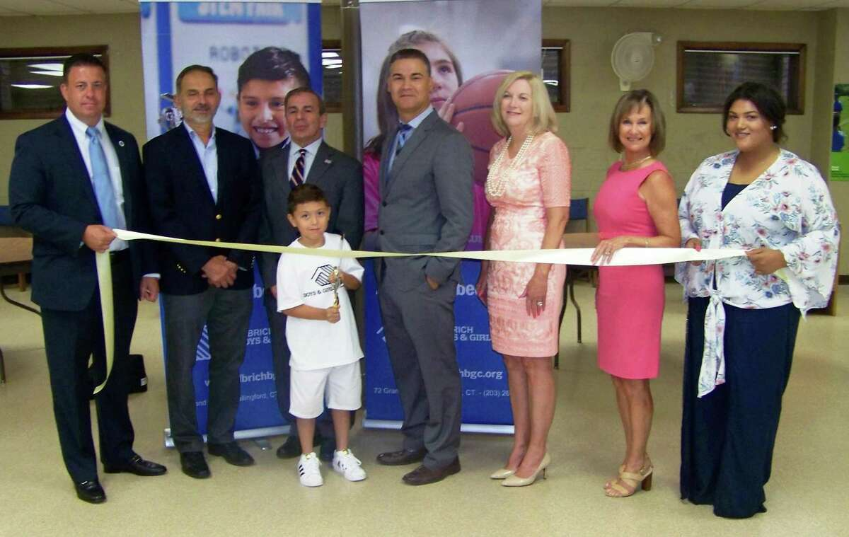 NEW LOCATION: From left, Ulbrich Boys & Girls Club board member Erik Scaranuzzo; state Rep. Dave Yaccarino; North Haven First Selectman Mike Freda; Carlos Collazo and son; UBGC board Chairwoman Tammie Ulbrich; Quinnipiac Chamber of Commerce Executive Director Dee Prior Nesti; and North Haven Unit Director Alexandra James celebrate the opening of an additional UBGC location at 211 Montowese Ave. in North Haven. The UBGC, based in Wallingford for more than 50 years, offers programs help young people achieve academic success, good character and citizenship and healthy lifestyles, according to a release. Visit www.ulbrichbgc.org.