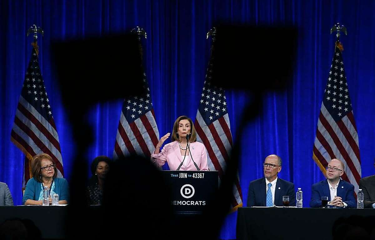 Nancy Mancias, with Code Pink, holds protest signs during a remarks by House Speaker Rep. Nancy Pelosi during a gathering of the Democratic National Committee summer meeting at the Hilton Hotel in San Francisco, Calif. on Friday, Aug. 23, 2019.