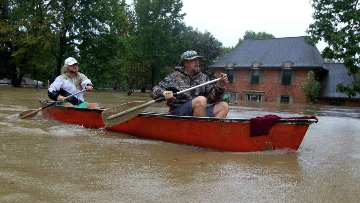 Josh and Levi Curnel float by their River Plantation home during Hurricane Harvey in 2017.