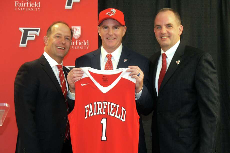 Jay Young, center, stands with university president Mark Nemec, left, and athletic director Paul Schlickmann after being introduced as the new men's basketball coach at Fairfield University, in April. Photo: Ned Gerard / Hearst Connecticut Media / Connecticut Post