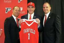 Jay Young, center, stands with university president Mark Nemec, left, and athletic director Paul Schlickmann after being introduced as the new men's basketball coach at Fairfield University, in April.
