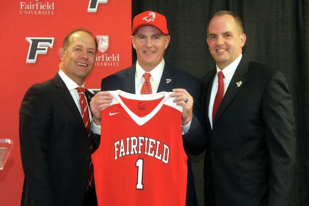 Jay Young, center, stands with university president Mark Nemec, left, and athletic director Paul Schlickmann after being introduced as the new men's basketball coach at Fairfield University, in Fairfield, Conn. April 10, 2019.