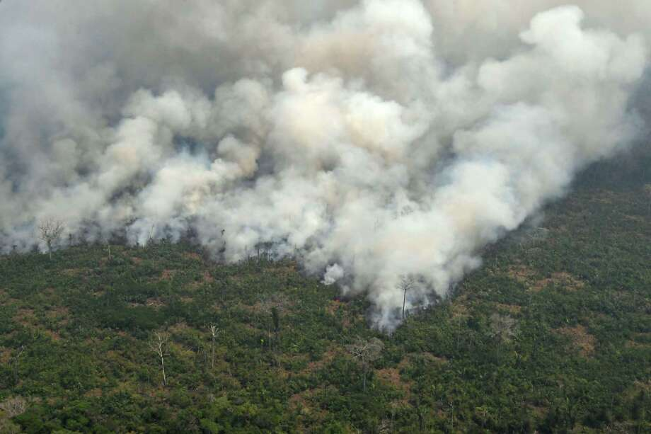 This aerial picture shows smoke from a two-kilometer-long stretch of fire billowing from the Amazon rainforest about 65 km from Porto Velho, in the state of Rondonia, in northern Brazil, on August 23. President Bolsonaro said Friday he is considering deploying the army to help combat fires raging in the Amazon rainforest, after news about the fires have sparked protests around the world. The latest official figures show 76,720 forest fires were recorded in Brazil so far this year — the highest number for any year since 2013. More than half are in the Amazon. Photo: CARL DE SOUZA / AFP /Getty Images / AFP or licensors