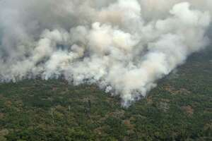 This aerial picture shows smoke from a two-kilometer-long stretch of fire billowing from the Amazon rainforest about 65 km from Porto Velho, in the state of Rondonia, in northern Brazil, on August 23. President Bolsonaro said Friday he is considering deploying the army to help combat fires raging in the Amazon rainforest, after news about the fires have sparked protests around the world. The latest official figures show 76,720 forest fires were recorded in Brazil so far this year — the highest number for any year since 2013. More than half are in the Amazon.