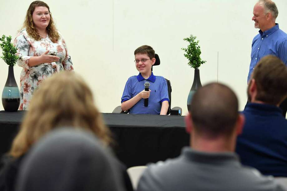 Born with spinal muscular atrophy, Benjamin Willis, center, talks about his life and future plans before presenting a check for more than $10,000 to the Muscular Dystrophy Association during an event at Mometrix in Lumberton Friday. The check stems from a years-long fundraiser that is nearing its goal of $100,000. Jay Willis, Benjamin's father, and Nicole Turvey are also pictured.   Photo taken Friday, 8/23/19 Photo: Guiseppe Barranco/The Enterprise, Photo Editor / Guiseppe Barranco ©