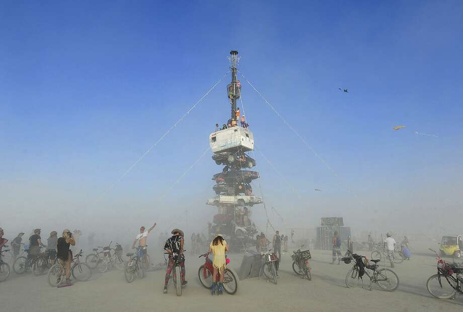 "FILE -  this Monday, Aug. 27, 2018 file photo, burners surrounded by playa dust climb onto an art installation titled, ""Night of the Climb,"" at Burning Man, in Gerlach, Nev. A man was arrested on charges of sexual assault and the false imprisonment of an unidentified victim at the Burning Man site on Thursday, just four days before this year's festival began. Photo: Andy Barron, Associated Press"