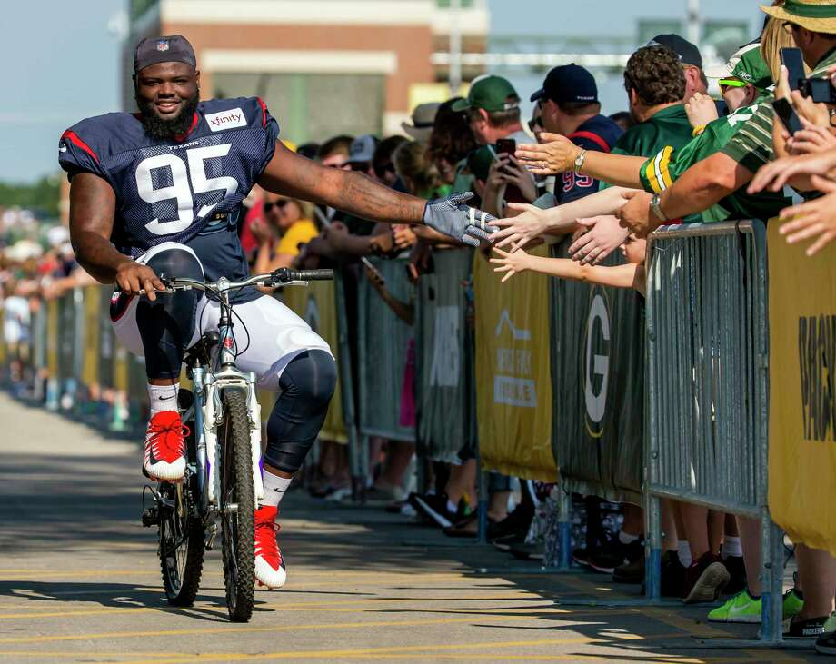 PHOTOS: Texans training camp Houston Texans defensive tackle Johnny Dwight, left, greets fans as he rides a bicycle to a joint NFL football practice with the Green Bay Packers, Monday, Aug 5, 2019, in Green Bay, Wis. (AP Photo/Mike Roemer) >>>See photos from the Texans' training camp Thursday, Aug. 22, 2019 ... Photo: Mike Roemer, Associated Press / Copyright 2019 The Associated Press. All rights reserved.
