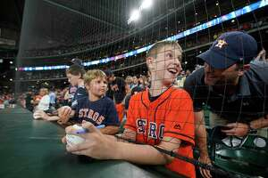 Wesley Walker, 9, talks to his dad, Russell Walker, after getting an autograph from Houston Astros Josh Reddick by reaching under the protective netting before MLB game against the Detroit Tigers at Minute Maid Park Monday, Aug. 19, 2019, in Houston. The Astros extended the netting inside Minute Maid Park in an effort to better protect fans from foul balls.