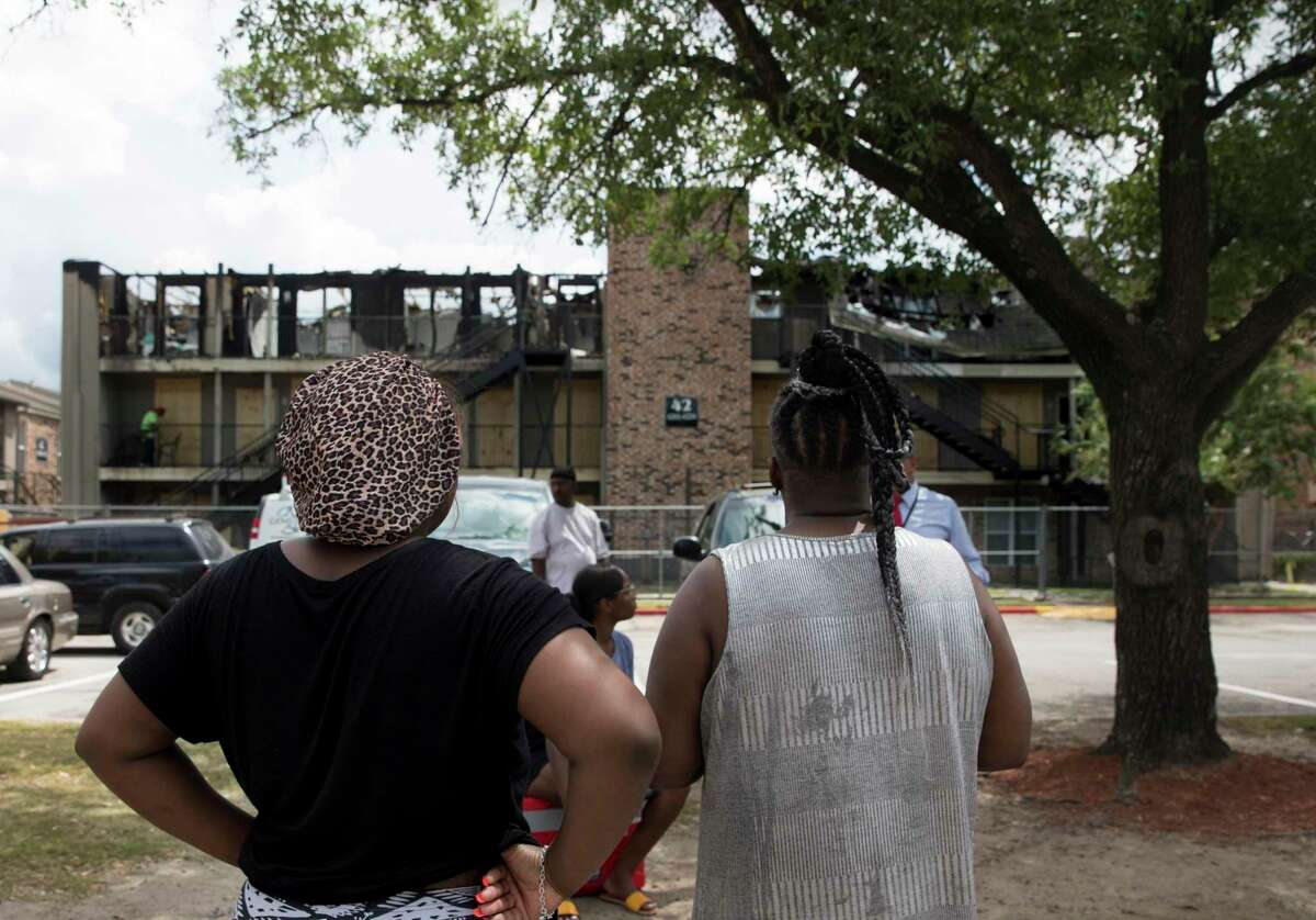 Displaced residents of the Haverstock Hills Apartments, located at the 5600 block of Aldine Bender Road, Ianna Mitchner, left, and Lisa Jenkins watch workers boarding up the burnt-down building and hope to have a place to stay on Friday, Aug. 23, 2019, in Houston. Both women lived on the third floor and were nextdoor neighbors. The two-alarm fire started before 1 a.m. amd 27 people were displaced