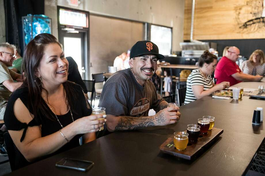 Maricela Gomez, left, and Ray Puentes enjoy a tasting flight of beer at High Water Taproom in Lodi. The taproom features 36 taps, a full kitchen and an outdoor beer garden. Photo: Laura Morton