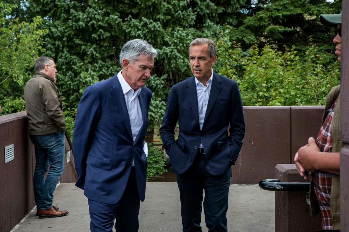 Federal Reserve Chairman Jerome Powell, left, and Bank of England Governor Mark Carney, right, walk together after Powell's speech at the Jackson Hole Economic Policy Symposium on Friday, Aug. 23, 2019, in Jackson Hole, Wyo. (AP Photo/Amber Baesler)