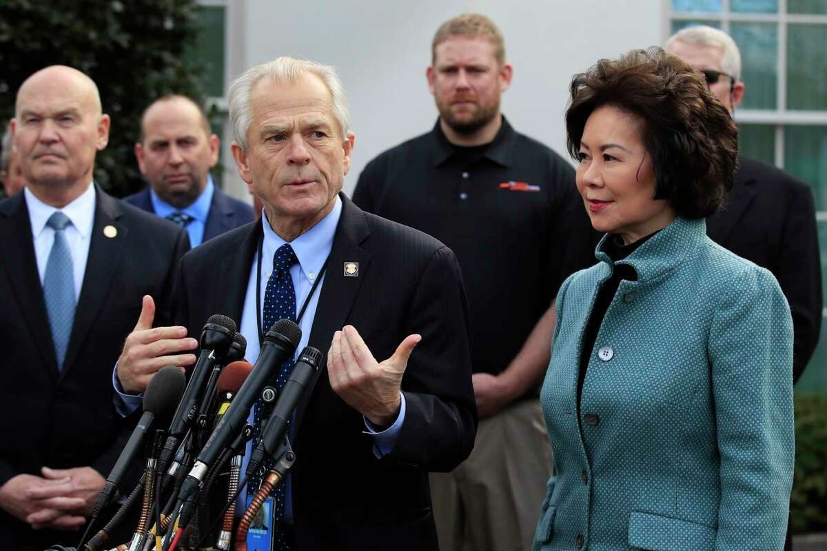 FILE - In this March 4, 2019, file photo, White House trade adviser Peter Navarro, front left, with Transportation Secretary Elaine Chao, right, and U.S. Maritime Administration Administrator Mark Buzby, back left, speaks to reporters outside the West Wing of the White House in Washington. Where past presidents have relied on top academics, business leaders and officials with experience in prior administrations, Trump has gone a different route. Hea€™s built crew of camera-ready economic advisers, rather than one known for its policy chops. (AP Photo/Manuel Balce Ceneta, File)