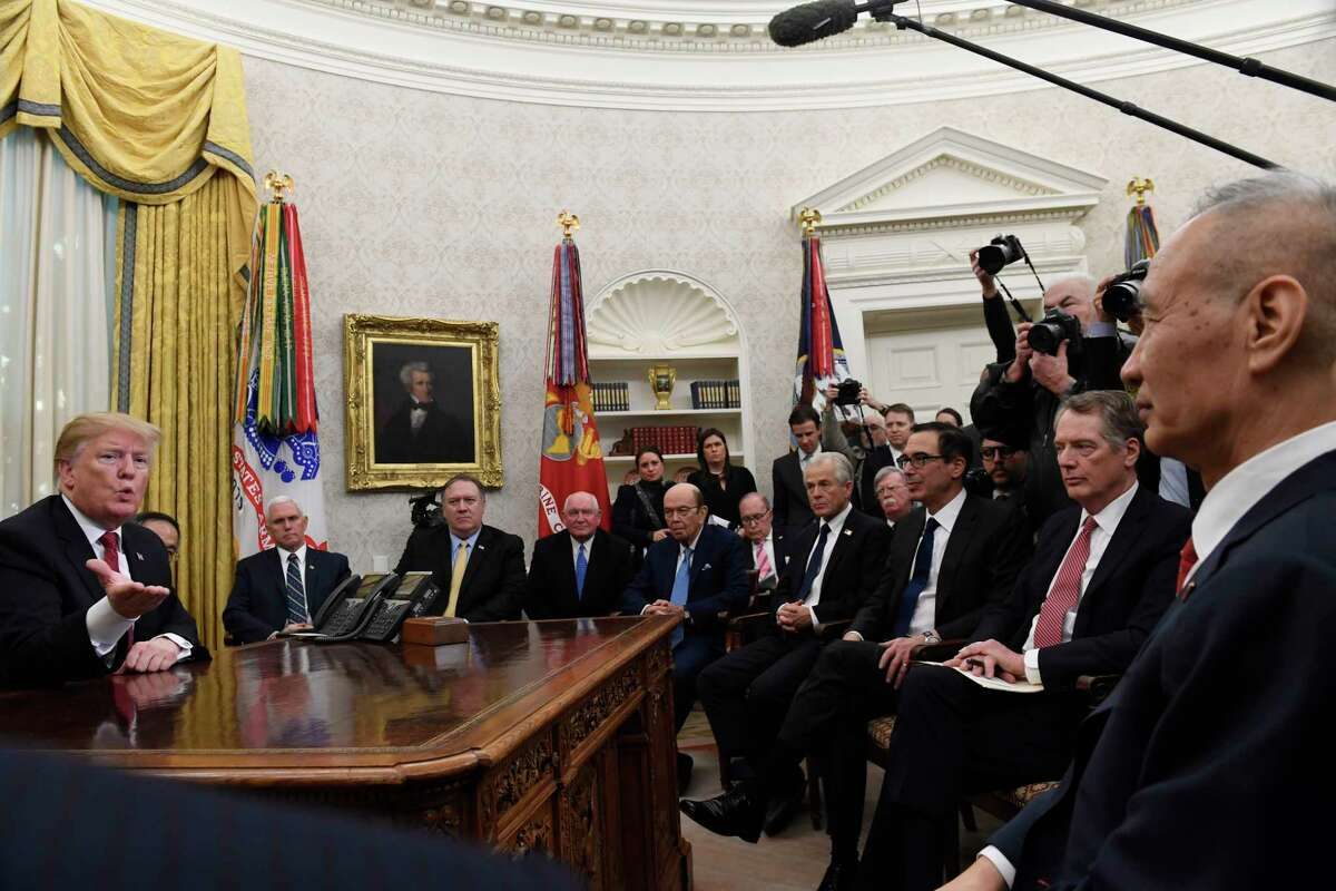 FILE - In this Jan. 31, 2019, file photo, President Donald Trump, left, holds a meeting with Chinese Vice Premier Liu He, right, in the Oval Office of the White House in Washington. Also attending the meeting, starting third from left seated, are, Vice President Mike Pence, Secretary of State Mike Pompeo, Agriculture Secretary Sonny Purdue, Commerce Secretary Wilbur Ross, White House economic adviser Larry Kudlow, White House trade adviser Peter Navarro, national security adviser John Bolton, Treasury Secretary Steven Mnuchin, and U.S. Trade Representative Robert Lighthizer. (AP Photo/Susan Walsh, File)