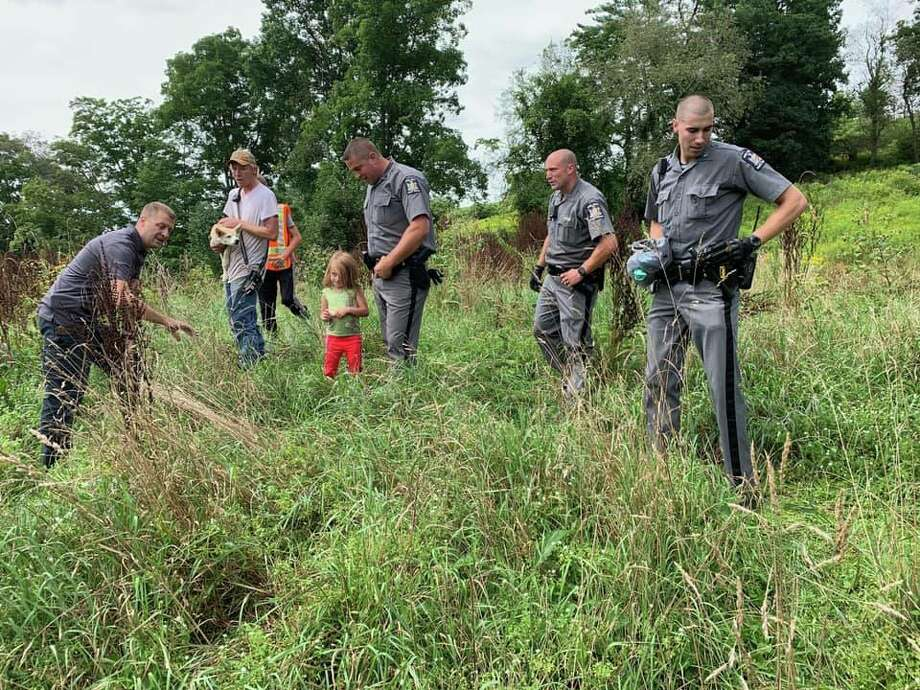 State troopers surround a 5-year-old girl and her dog, who both went missing in Franklin, N.Y., on Friday, Aug. 23, 2019, and were found together and safe hours later. Photo: State Police