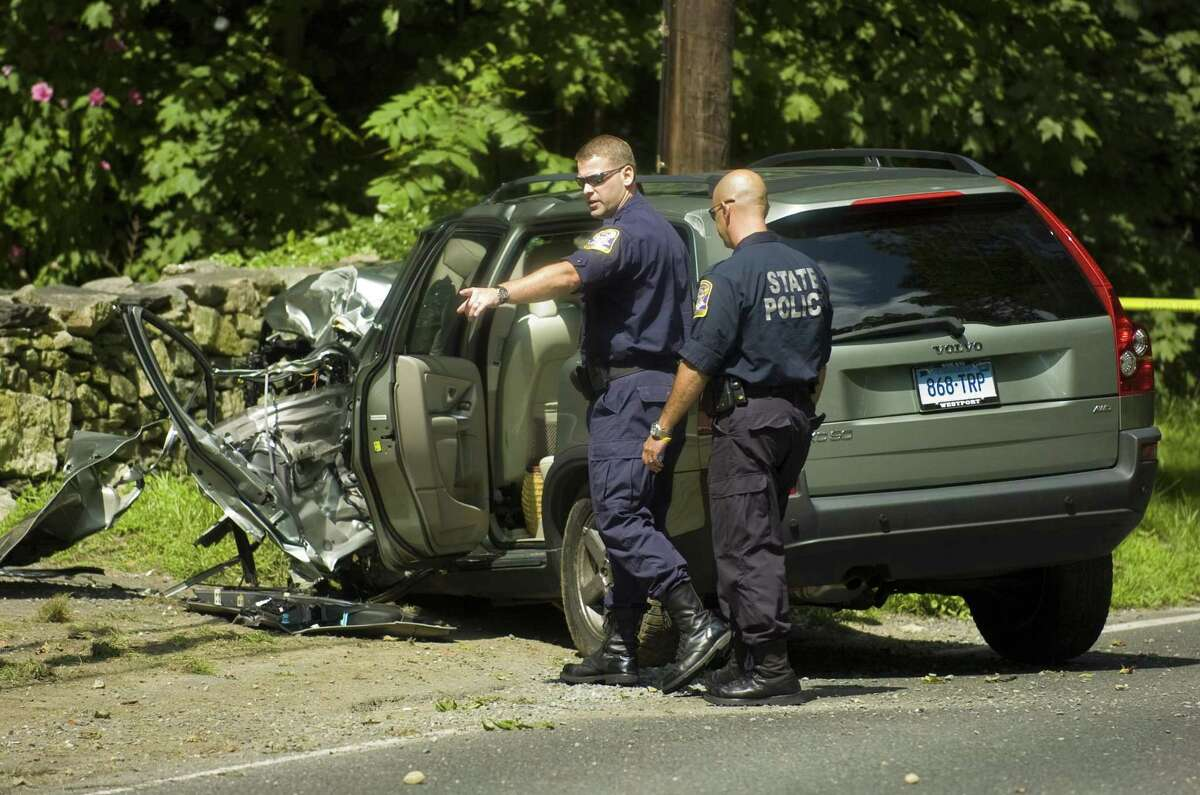 Connecticut State Police troopers Brian Martini, left, and Joe Russo, right of the collision analysis squad inspect the scene after a suspected carjacking suspect crashed a vehicle on Weston Road in Weston, Conn. on Tuesday, August 25, 2009. The unidentified man was suspected in three carjackings in Norwalk and Westport on Tuesday. He was transported to Norwalk Hospital, where he died. Chris Preovolos / Staff Photographer