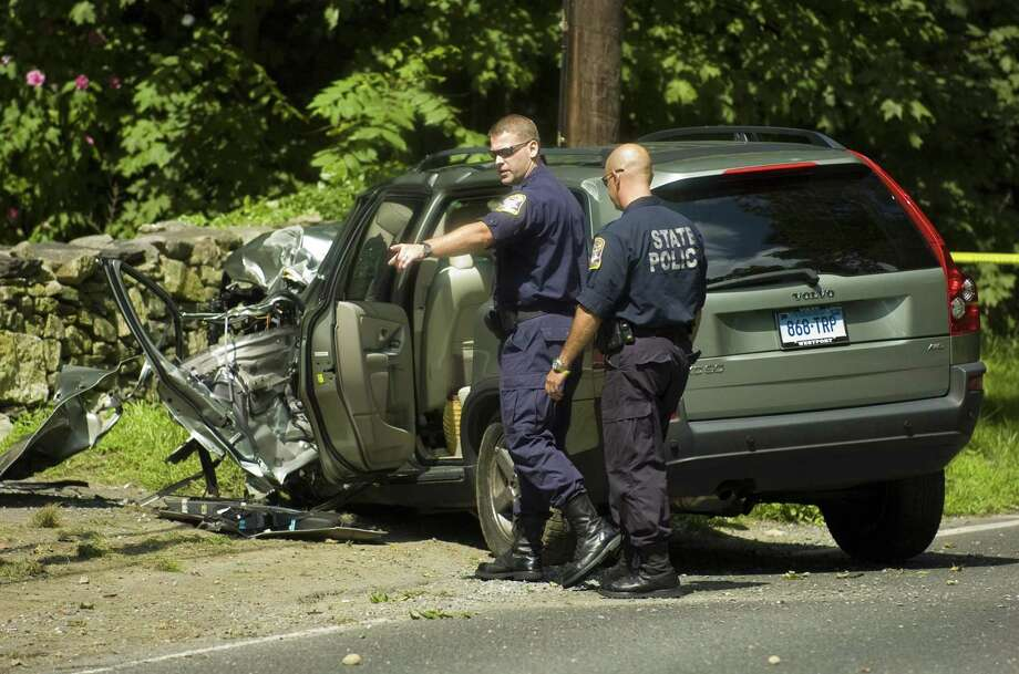 Connecticut State Police troopers Brian Martini, left, and Joe Russo, right of the collision analysis squad inspect the scene after a suspected carjacking suspect crashed a vehicle on Weston Road in Weston, Conn. on Tuesday, August 25, 2009. The unidentified man was suspected in three carjackings in Norwalk and Westport on Tuesday. He was transported to Norwalk Hospital, where he died. Chris Preovolos / Staff Photographer Photo: Chris Preovolos / ST